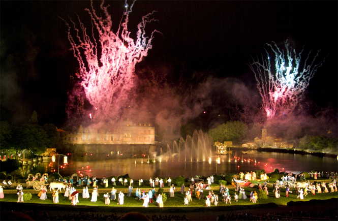Fireworks going off behind performers onstage at the Cinéscénie event at Puy du Fou theme park. The French park has been the subject of controversy it was allowed 9,000 visitors on Saturday evening.