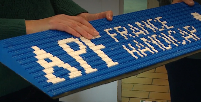 A volunteer holds up a ramp made of Lego. Lego wanted to help make wheelchair ramps in eastern France