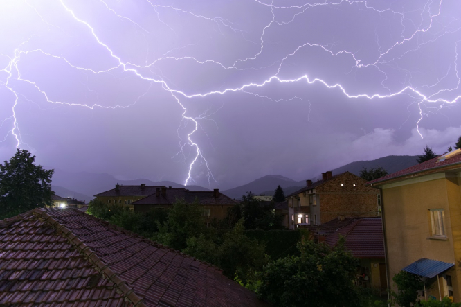 A lightning strike above houses. Houses in France struck by lightning as storm alerts remain