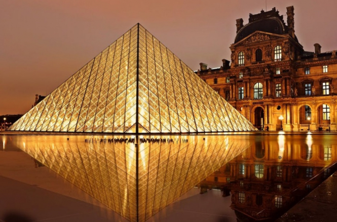 The pyramid of the Paris Louvre at night. Paris Louvre reopens after Covid closure: Why now is a good time to visit