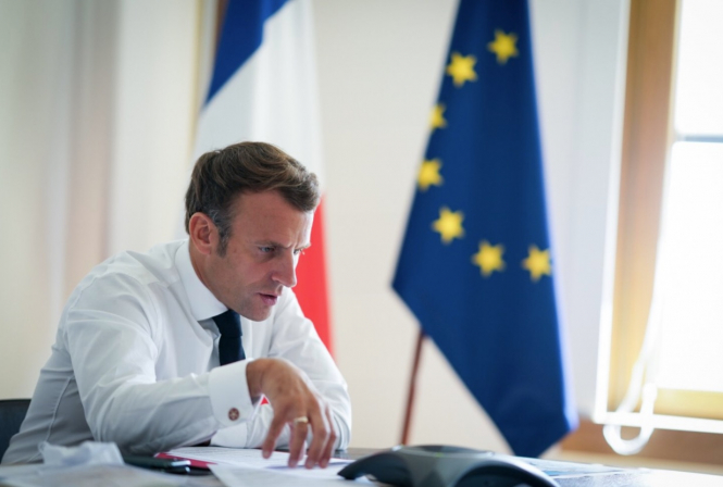 President Macron in front of French and European flags. Covid: EU to discuss new variants as France debates lockdown