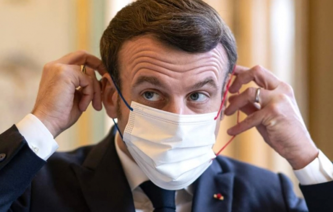 President Macron putting on a mask. Macron speech: 3 scenarios for new Covid rules in France under review