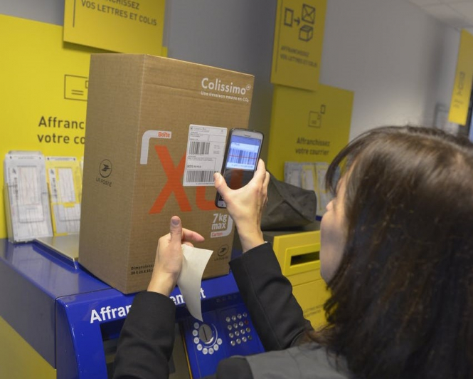 An employee at La Poste scans a barcode on a package. Article: Mail is at an all time high and La Poste are struggling. Photo from Connexion October print edition