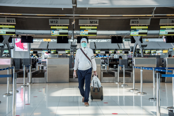 Man in a mask walking through an empty airport. Which countries have a quarantine in place for travellers from France?
