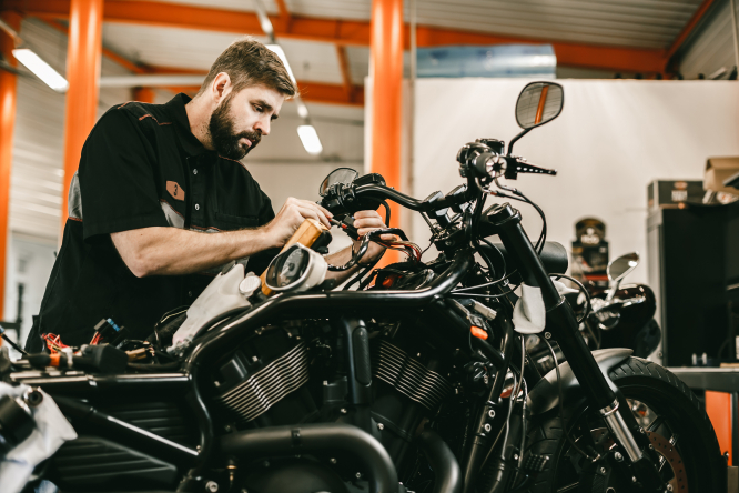A picture of a man repairing a motorbike