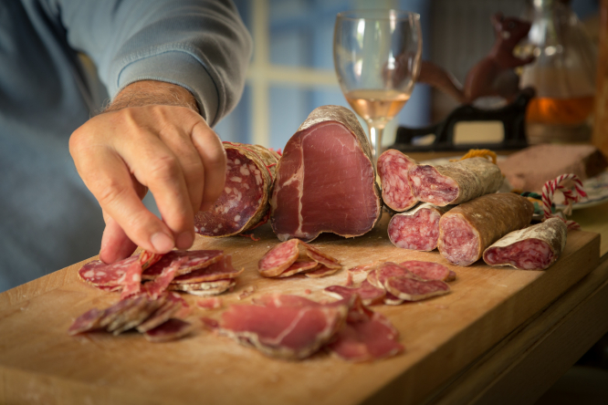 Man taking a slice of saucisson. France recalls dried meats after salmonella scare