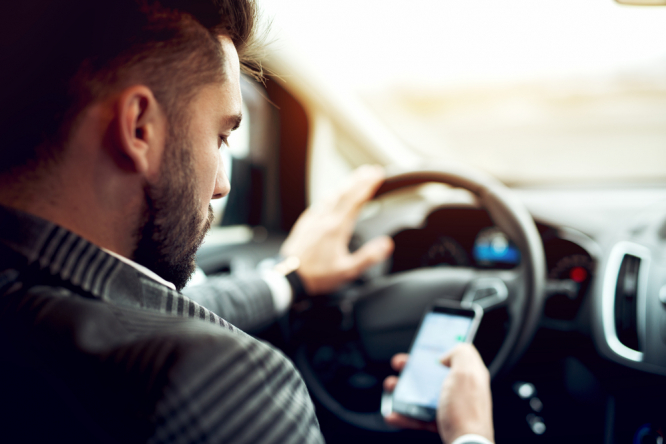 A man using a mobile phone while driving. France tests speed cameras that also check phone and seatbelt use