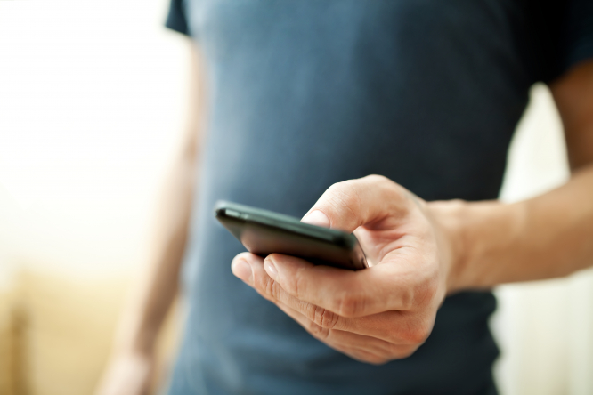 An image of a man holding a mobile phone