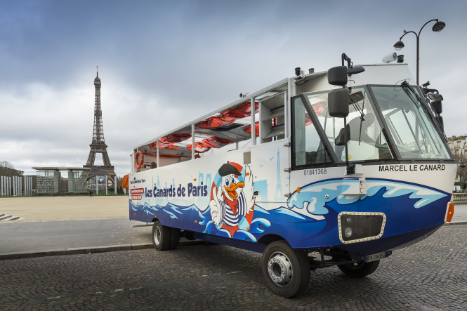 An image of the amphibious boat, Marcel le Canard, in front of the Eiffel Tower