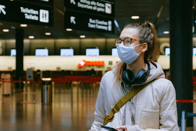 A woman wears a mask in an airport. What do European and International border reopening plans mean for France?