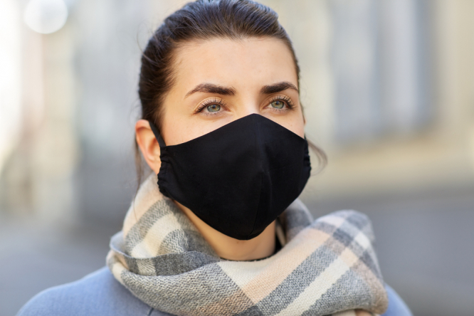 A woman wearing a mask and a scarf outdoors. New variant risk for France this winter, says top Covid advisor