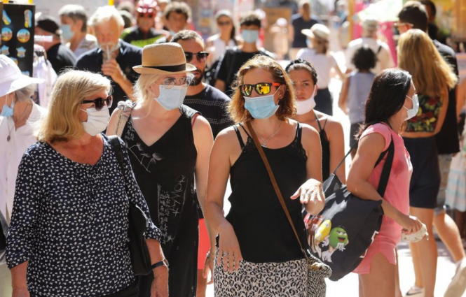 People wear masks in a busy street. Rise in mask-related violence in France as rules imposed