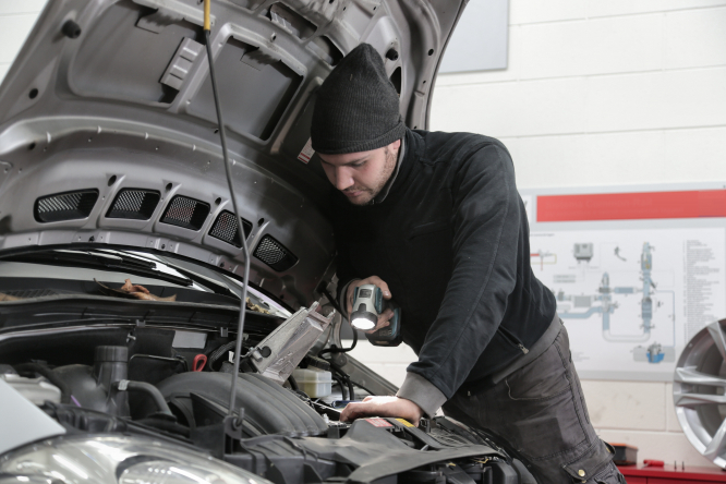 A mechanic looking under the bonnet of a car. A new price comparator for French MOT tests has been launched by the government.