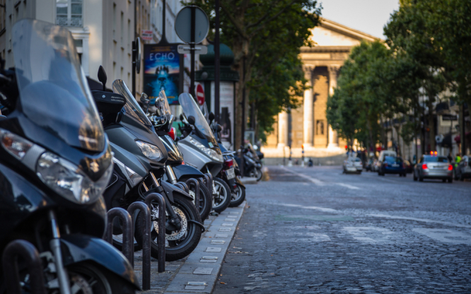 Motorbikes parked on a Paris street. Paris street parking fees set to rise 50% and motorbikes must pay too