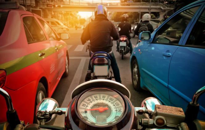 Motorbike travelling between cars. Motorbike lane filtering reintroduced in 21 French departments