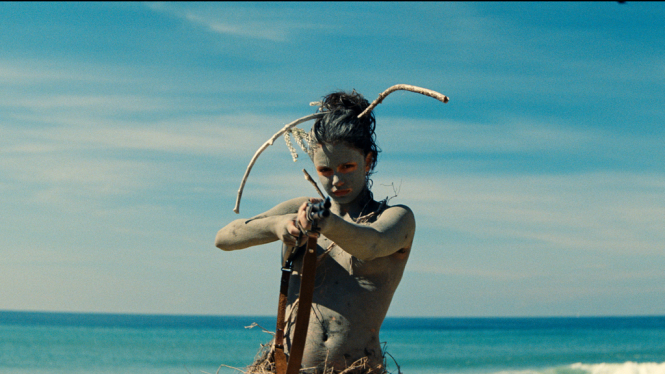 A 13-year-old girl plays with a bow and arrow on a beach with blue sea and blue sky behind