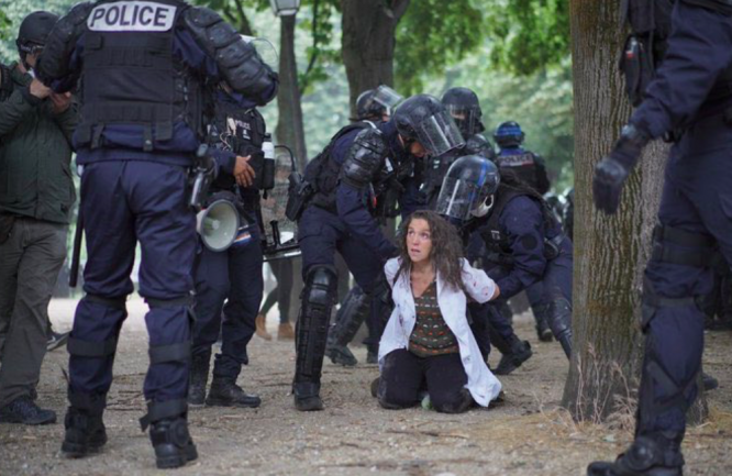 A nurse kneeling on the ground being arrested by police officers. The arrest in Paris has sparked accusations of police violence