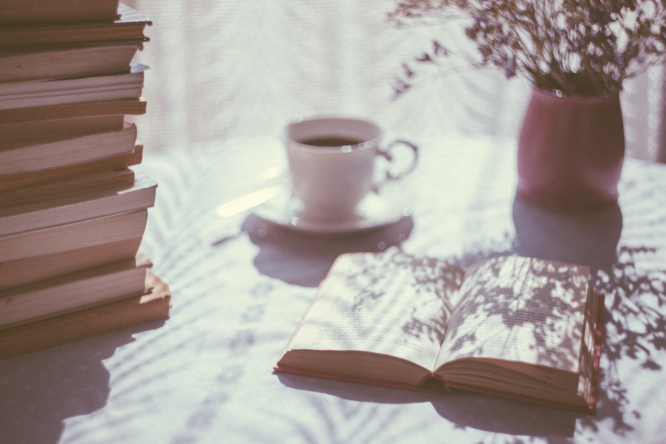 Open book on a table with a cup of tea. Article: October book reviews. Freestocks / Unsplash