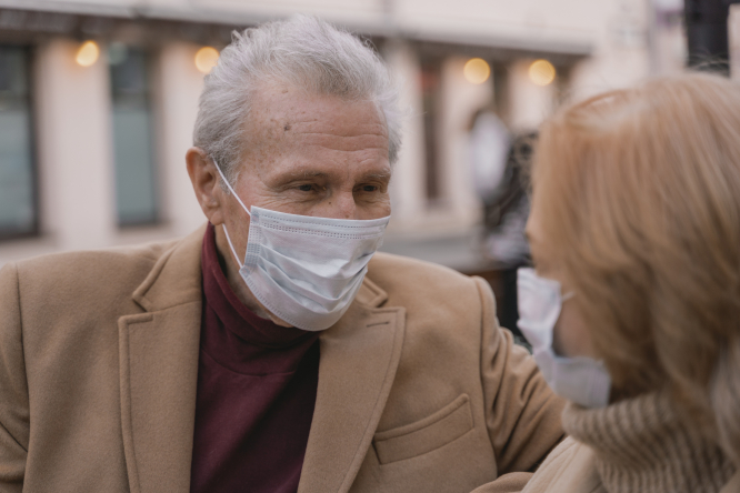 An older man wearing a mask. Covid cluster found among 11 vaccinated pensioners in French care home