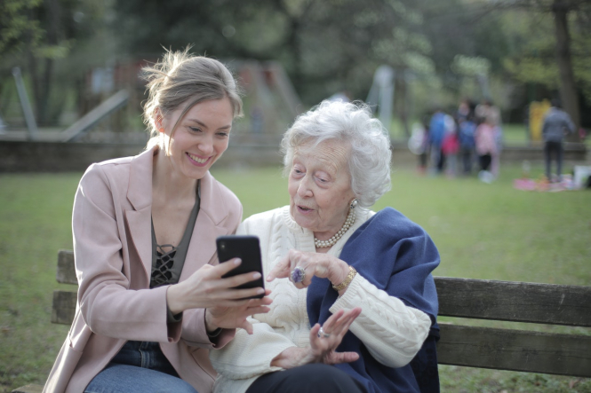 An elderly woman with a younger woman, looking at a smartphone. Vaccinations to begin for over 75s in France: How-to guide