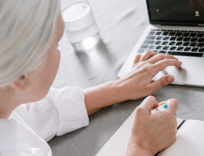 An older woman uses a computer. Covid vaccine: Pensioners in France struggle to book slots