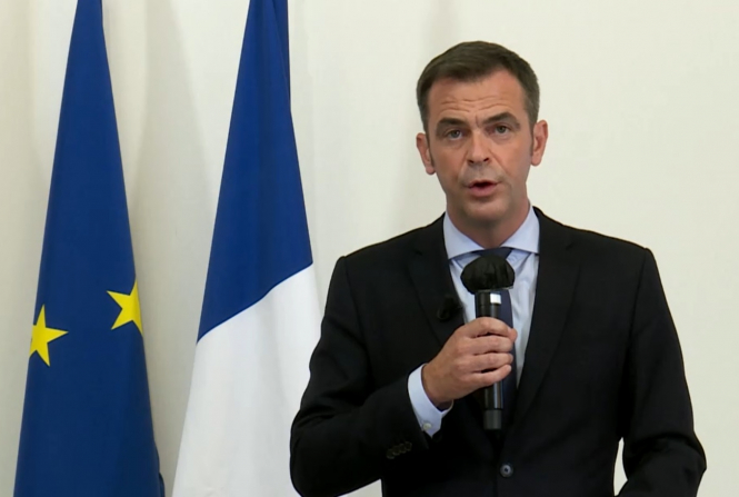Health minister speaks into a microphone in front of European and French flags. France Covid-19 update: More rules, masks and priority tests