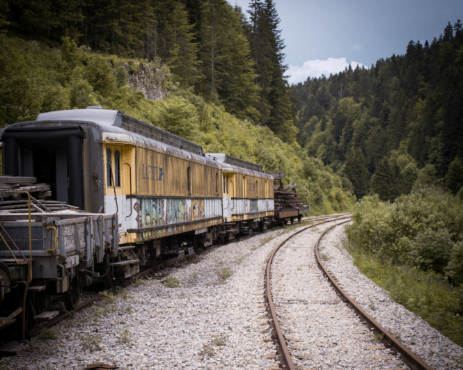 Photo: an old train on tracks with a view of a forest in the background, in Pontarlier, France. Article: New laws and changes in France, October 2020. Photo by Baptiste Gousset / Unsplash