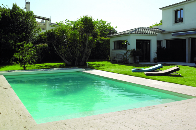 A garden with a pool, grass and trees. Our guide to owning a swimming pool in France. Desjoyaux / ©piscinesdesjoyaux