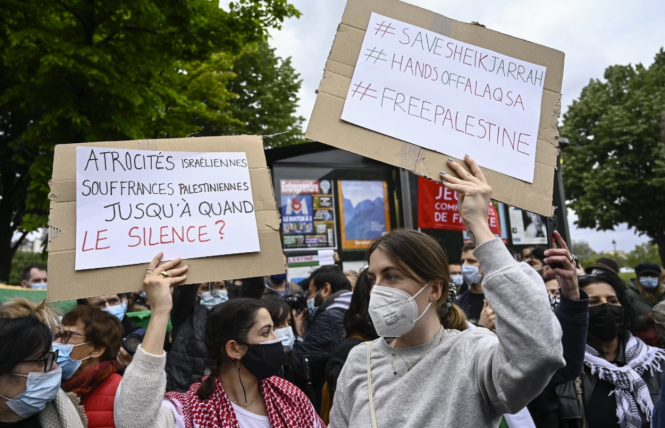 Masked women hold pro-Palestine placards in French during protests. Pro-Palestine marches take place across France