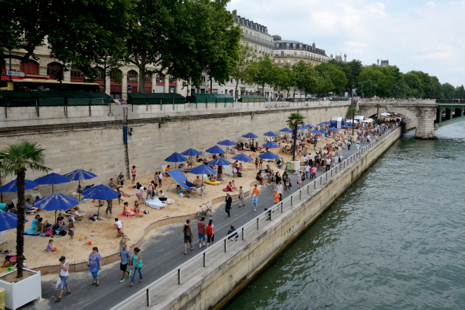 People enjoy a sandy beach on a road beside a river