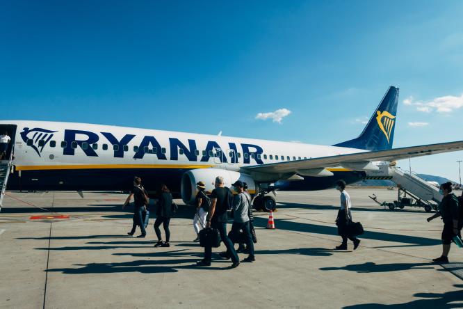 Passengers board a Ryanair flight. Air France and Ryanair trial digital passes for Covid travel