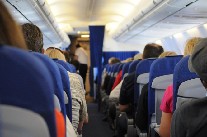 Passengers seated on a plane. French CEO says Covid tests, not vaccine, will save air travel