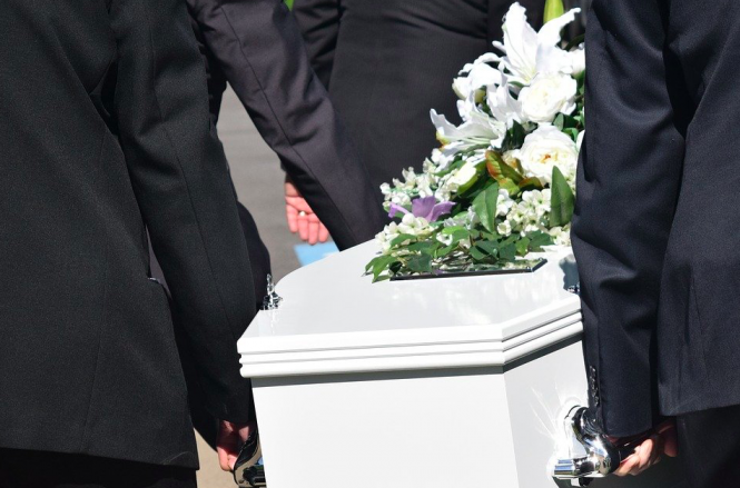People carrying a coffin with flowers. France lockdown: Can I travel back to the UK for a funeral?