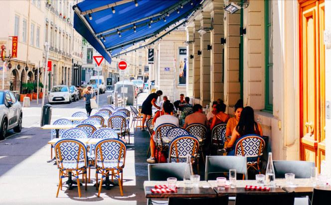 People eating on sunny terrace. Macron: Terraces and museums to reopen from mid-May across France