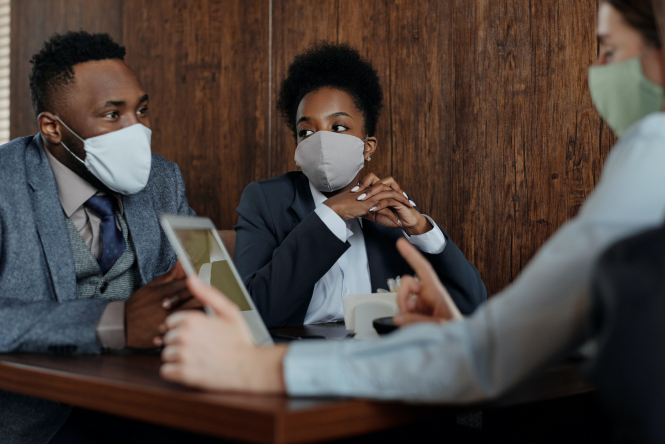 A group of people in an office wearing suits and medical masks. Medical masks will be mandatory at work from August in France