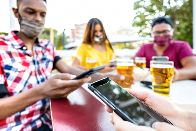 People using their phones in a bar. Covid-19 France: How does backwards contact tracing work?