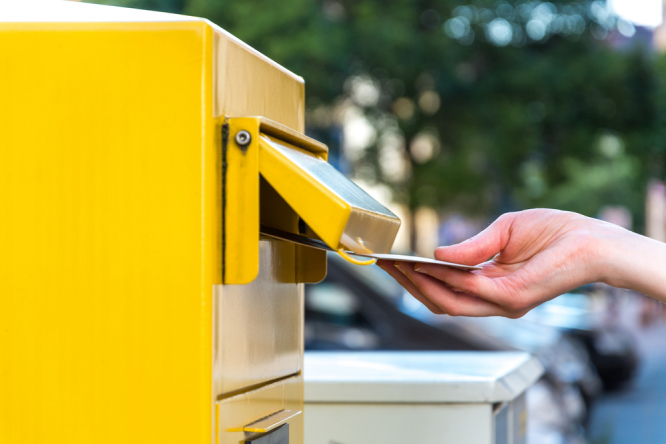 Person posting letter in yellow post box. French postal service to slow second-class delivery times by one day