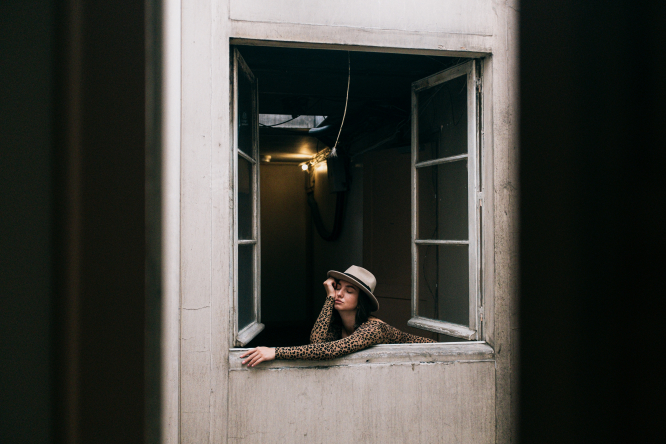 A woman self-isolating at home looks out a window
