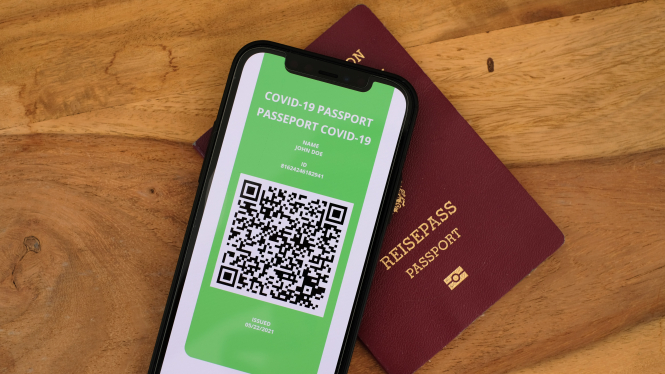 Phone with QR code and EU passport. EU digital health pass for summer travel available from June 15