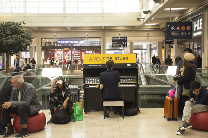 French man playing piano for show French people and foreigner travellers at Gare de Paris-Est or Paris Gare de l'est railway station on September 7, 2017 in Paris, France.  Pianos to return to French train stations with 50-player concert
