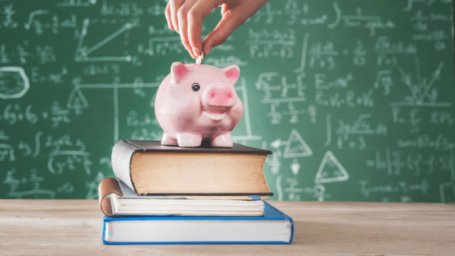 A woman puts coins into a piggybank on top of books, with a blackboard behind it. Back to school financial grant is on the way to 3 million French homes