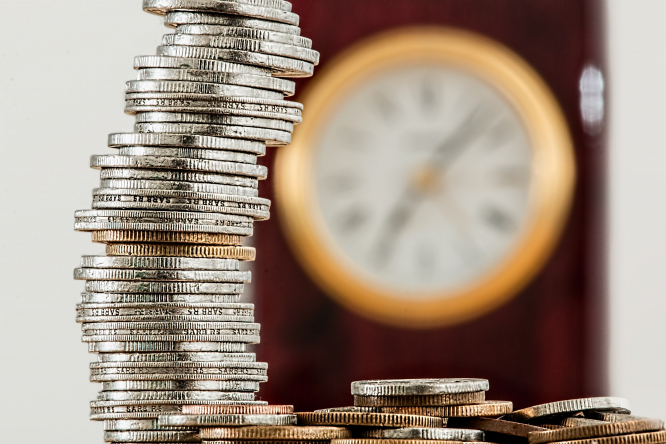 A pile of coins with a clock in the background. France gives financial aid to self-employed following the Covid-19 crisis.