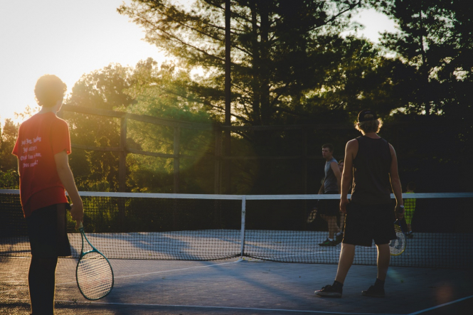 A group of people play tennis outside in a court. France lockdown: You can now go beyond 10km for (some) sport reasons
