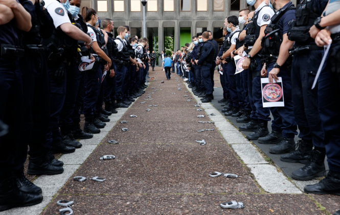 Police stand in two lines with their handcuffs on the ground in front of them. French police have rejected new 'anti-racism' announcements from Christophe Castaner by symbolically downing handcuffs