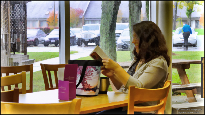 A woman sitting at a table in a cafe reading a book