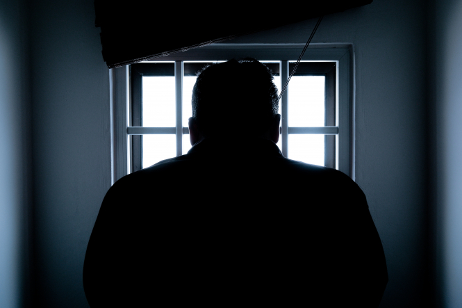 Man bows his head in a dark prison. Support for death penalty highest in France for six years