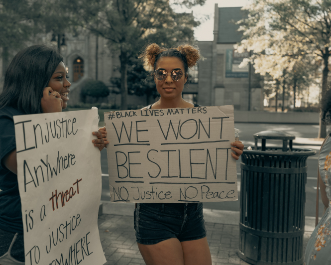 Protesters in Charlotte, NC, USA. Signs read: #blacklivesmatter, we won't be silent, no justice no peace, and inequality anywhere is a threat to justice everywhere.
