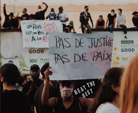 "A protestor in Paris on June 2, 2020, holding a sign that reads ""no justice, no peace."" Over 20,000 people attended the black lives matter protest in Paris"