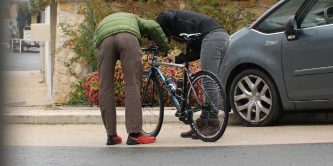 Men bend over bicycle