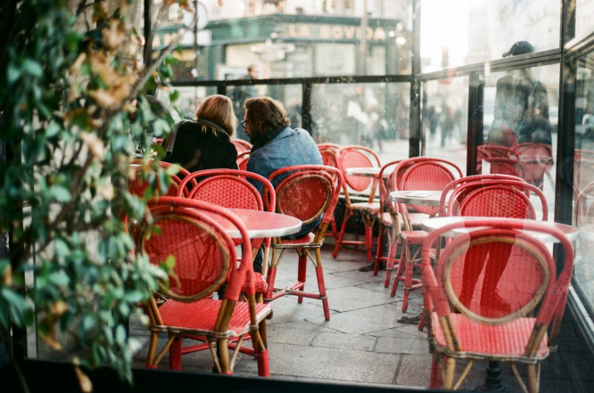 A couple sit outside on a restaurant terrace. Restaurant bookings in France soar ahead of May 19 reopening